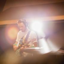 Guitarist recording song in music studio